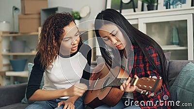 La ragazza afroamericana sorridente sta insegnando al suo amico asiatico a giocare la chitarra acustica che parla poi dando il su video d archivio