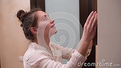 La ragazza appende un telaio sulla parete stock footage