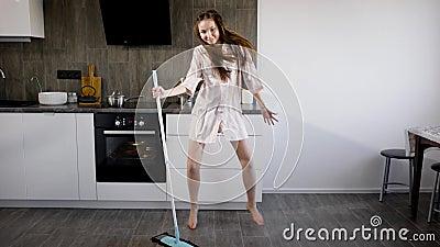 La ragazza divertente sta divertendosi quando fa la pulizia della casa, il dancing esagerato intorno alla scopa in cucina stock footage