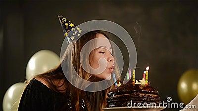 La ragazza emozionale felice spegne le candele durante la celebrazione il suo compleanno ed applaude Chiuda sul ritratto della gi video d archivio