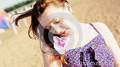 La ragazza felice sulla spiaggia con il fiore sorride in camera sunny carefree ballo stock footage