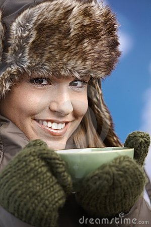 La ragazza graziosa ha vestito in su sorridere bevente caldo del tè