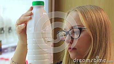 La ragazza nel dipartimento della latteria sceglie il latte stock footage
