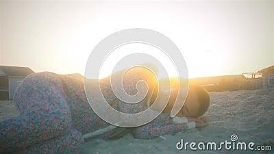 La ragazza in pigiami che fa un sonnellino sulla spiaggia al tramonto circondata librandosi gulls video d archivio