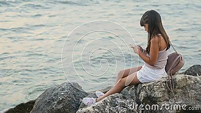 La ragazza utilizza il telefono al mare stock footage