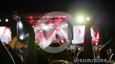 La scena di Lit tramite l'illuminazione colourful durante il festival rock di notte, molte luci in scena, la gente applaude sulla video d archivio