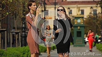 La señora joven del negocio muestra las ventanas de un objeto de las propiedades inmobiliarias a su cliente en un parque almacen de metraje de vídeo