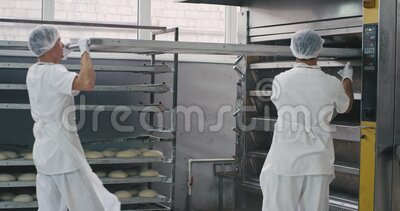 La sección de panadería de la industria alimentaria, dos trabajadores profesionales con un uniforme blanco de equipo especial, ca almacen de metraje de vídeo