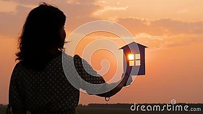 La silhouette d'une fille dans une robe tenant une maison en papier Beau coucher de soleil la nuit Le bonheur et le confort de la banque de vidéos