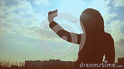 La silhouette d'une jeune femme avec des verres sur la nature prend un selfie contre le contexte du coucher du soleil et des bâti banque de vidéos