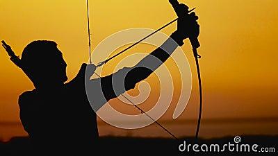 La silueta del tiro al arco, sol fija detrás del arquero Cazador joven almacen de metraje de vídeo
