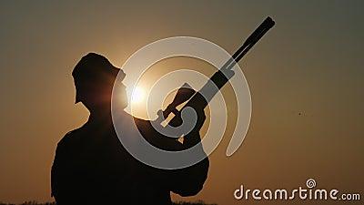 La siluetta di un cacciatore con una pistola, i raggi del sole splende nel suo fronte stock footage