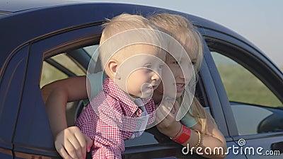 La soeur aînée et son petit frère regardent par la fenêtre d'une voiture et sourient Concept de voyage banque de vidéos