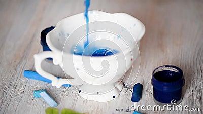 La tazza è l'acqua colorata blu versata Disegno, creatività stock footage
