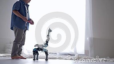 La tecnología de la innovación en niñez, muchacho lindo del niño es jugada por el juguete del robot en teledirigido usando el tel almacen de video