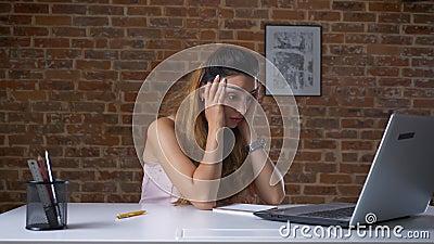 La travailleuse active fatiguée utilise son ordinateur portable, dactylographiant tout en se reposant au bureau au-dessus du mur  banque de vidéos