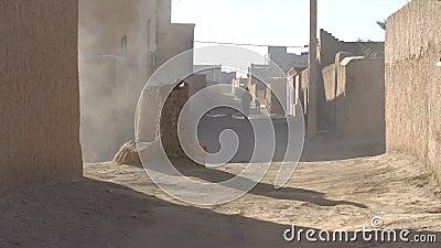 La via ha sparato il vicolo nel villaggio dell'argilla nel Marocco, Africa Un uomo in djellaba facendo uso del tubo flessibile de stock footage