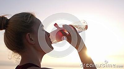 La vista lateral de la muchacha hermosa en ropa del deporte abre su botella coloreada rosada del deporte y agua potable después d metrajes