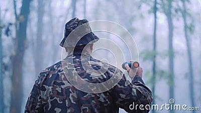 La vue arrière d'un homme en camouflage, c'est marcher dans la forêt, allumer son chemin dans le brouillard Rechercher le manquan banque de vidéos