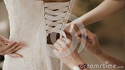 La vue en gros plan de la jeune mariée de aide de main femelle met dessus la robe Robe de mariage de laçage de demoiselle d'honne banque de vidéos