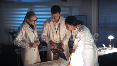 Laboratorio de investigación de la tecnología: Cierre medio para arriba del equipo diverso de los ingenieros que hace análisis en almacen de video