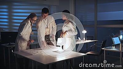 Laboratorio de investigación de la tecnología: Grupo diverso de ingenieros que discuten el desarrollo de la electrónica con la pl almacen de metraje de vídeo