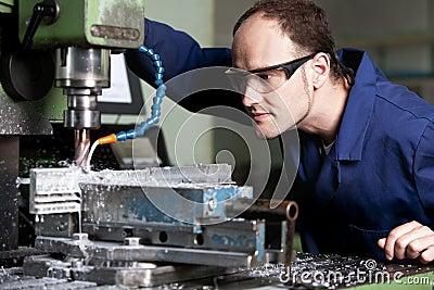 Laborer at milling machine.