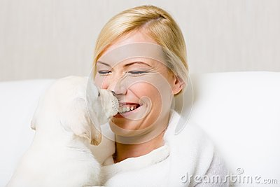 Labrador puppy licking the face of woman