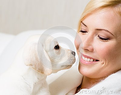 Labrador puppy and woman look at each other