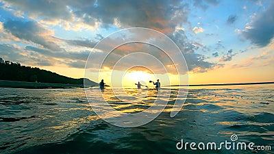 Lac Sunset avec des bateaux en canoë au ralenti banque de vidéos