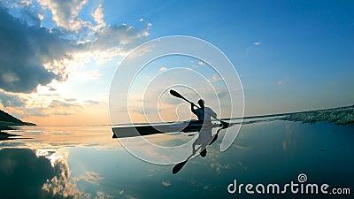 Lac Sunset avec une pagaie mâle qui le traverse banque de vidéos