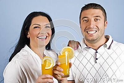Lachende gesunde Paare mit Orangensaft