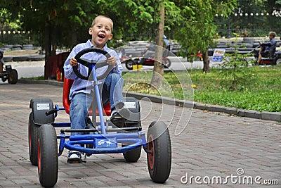 Lachende jongen in een pedaalkar, die pret heeft