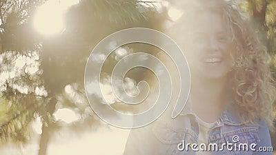 Lachende junge Dame in den Abdeckungen einer Jeansjacke ihr Gesicht mit ihrem gelockten Haar, deckt dann ihr schönes Lächeln auf  stock video