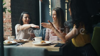 Lachende meisjesvrienden die handen in koffie samenbrengen die van vriendschap genieten stock videobeelden