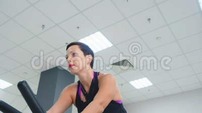 Lachende vrouw training binnenfiets op fietsklasse in gym Fijne vrouw fietst op fitnesstraining in een lage hoek stock footage