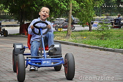 Lachender Junge in einem Pedalwagen, Spaß habend