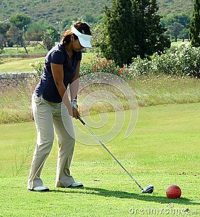 Lady golfer teeing off.