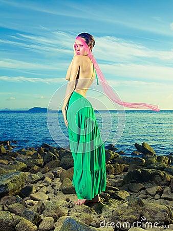 Lady in green dress on seashore