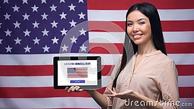 Lady Holding Tablette mit Lernerfahrung Englisch App, US-Flagge auf Hintergrund, Bildung stock footage