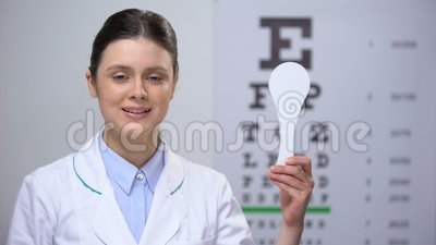 Lady oculist holding tool for auge close, special instrument of sight test stock video footage