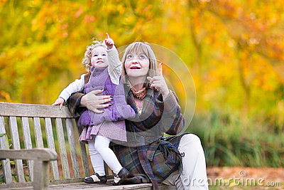 Lady playing with little toddler girl in autumn park