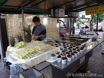 Lady prepares food at food stand on sidewalk Editorial Photography