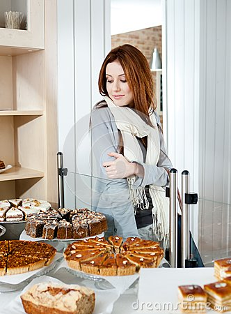 Lady in scarf looking at the bakery glass case