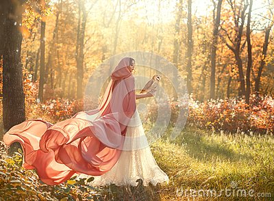 lady in shiny white dress and peach pink cloak with long train and hood Stock Photo