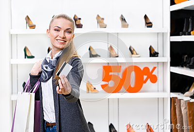 Lady showing credit card in footwear shop