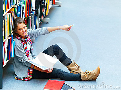 Lady sitting in the library pointing at something