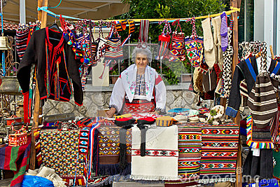 Lady in traditional clothes selling on booth Editorial Stock Image