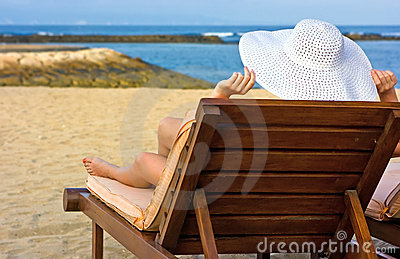 Lady in white hat on the beach