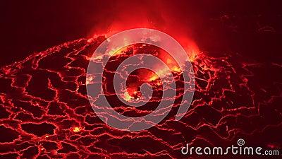 Lago de fusión rojo caliente enorme de la lava que entra en erupción en el cráter Congo África del volcán activo de Nyiragongo en metrajes
